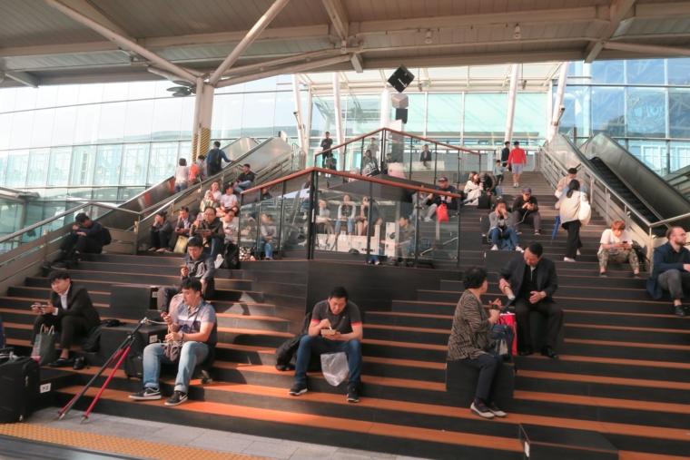 駅の中で座る人たち